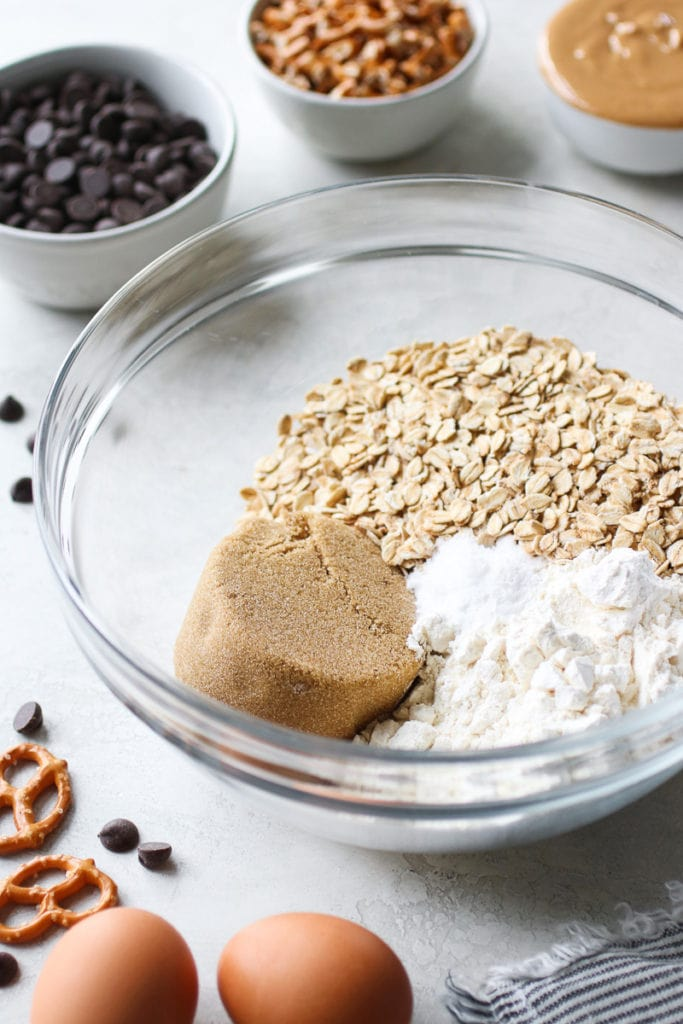 A clear glass bowl with oats, flour, brown sugar, and baking powder.
