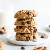 A stack of four Peanut Butter Chocolate Chip Pretzel Cookies on a white plate with a glass on milk in the background.