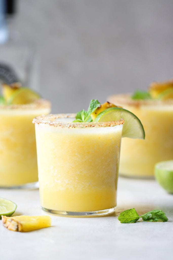 Photo of Frozen Pineapple Margaritas - three servings garnished with a fresh mint leaf, lime slice and pineapple wedge.