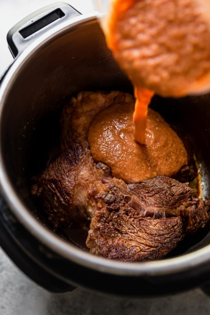 Sauce pours from a blender container onto a seared beef chuck roast in an Instant Pot.