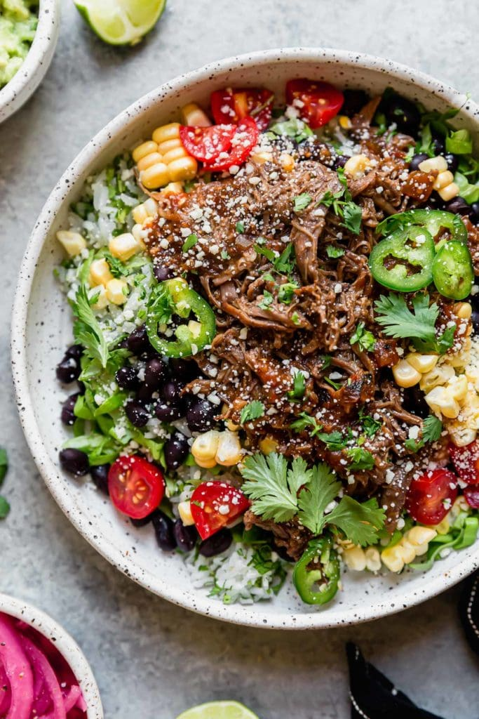 Overhead view of slow cooker beef barbacoa on a bed of lettuce, corn, tomatoes, rice, and topped with cilantro and jalapeno slices.