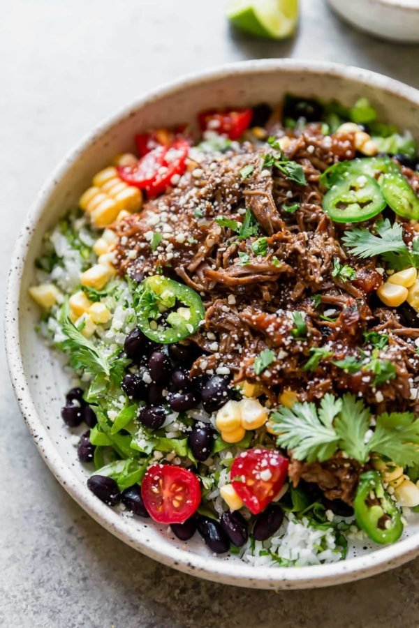 Burrito bowl made with Instant Pot Beef Barbacoa, served on a white plate.