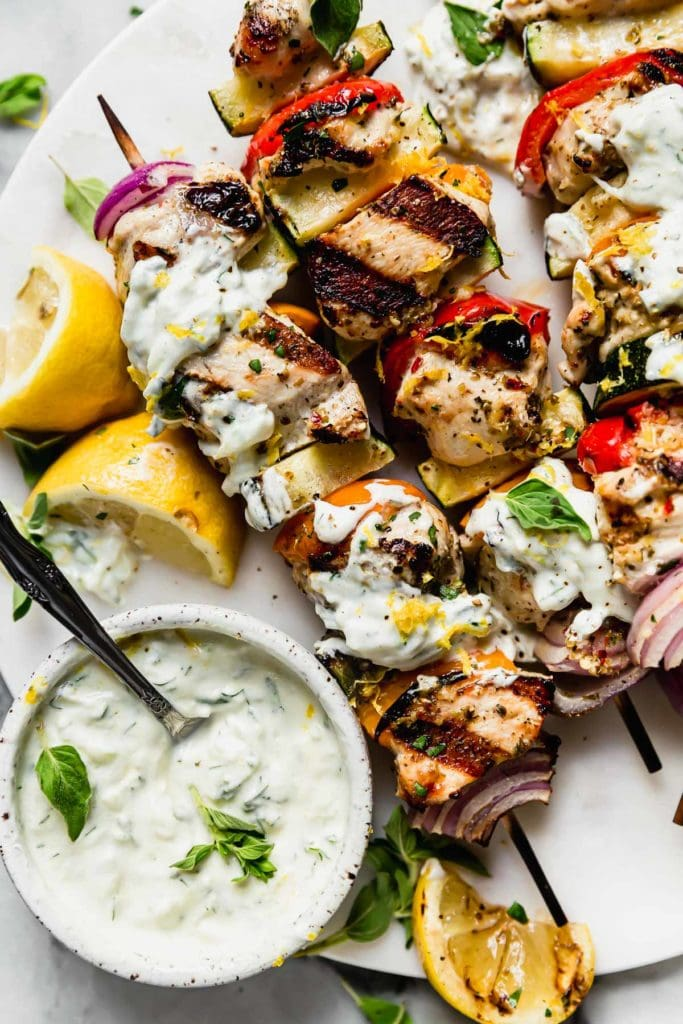 Greek chicken kebobs slathered in homemade Tzatziki sauce plated on a white plate