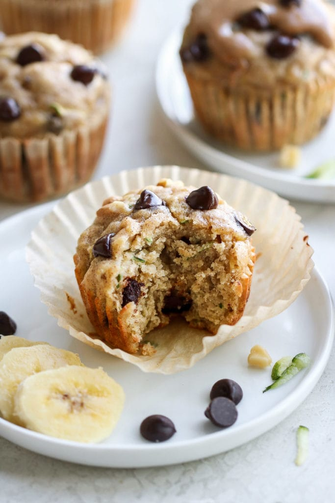 Photo of Gluten-free Chocolate Chip Zucchini Muffins - one of the muffins on a plate with a bite out of it.