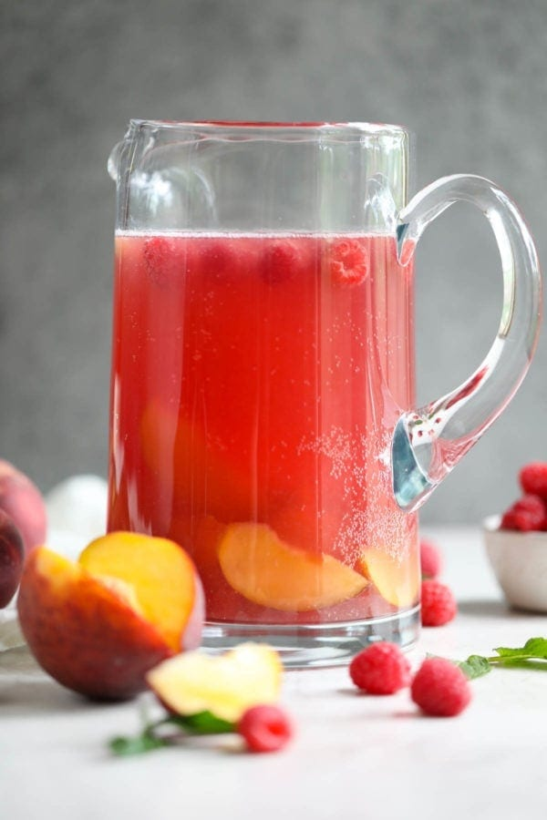 A tall glass pitcher of Raspberry-Peach Rosé Sangria with a grey backdrop.