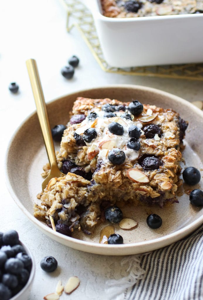 Blueberry Baked Oatmeal topped with whipped topping, drizzled with maple syrup on a small tan plate with a gold fork holding bite.