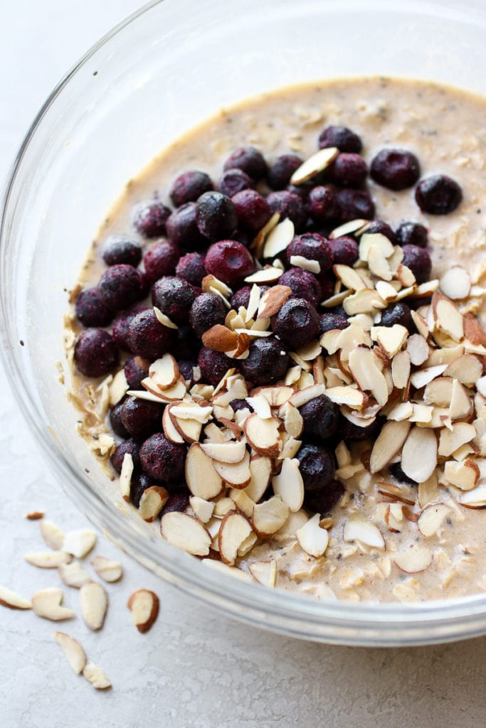 Blueberry Baked Oatmeal ingredients mixed in a bowl with sliced almonds and blueberries onto ready to be mixed in.