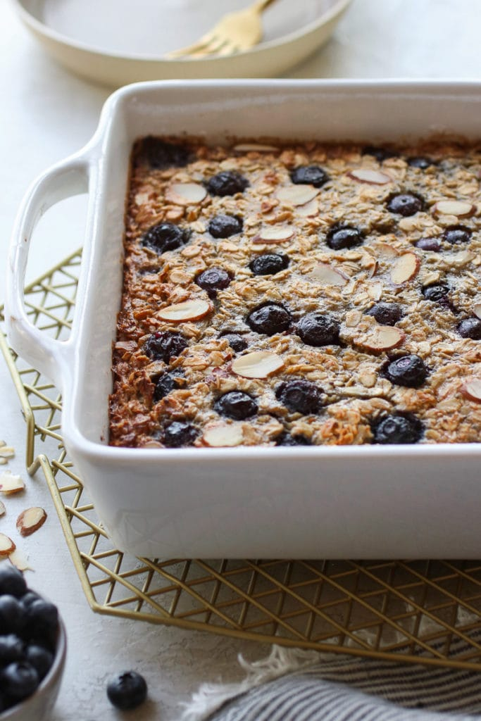 Blueberry Baked Oatmeal in a white baking dish right out of the oven sitting on a gold wire cooling rack.