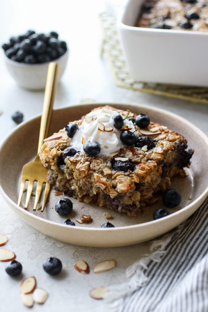 Healthy Blueberry Baked Oatmeal topped with whipped topping on a small tan plate with a gold fork resting on the plate.