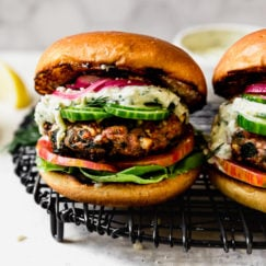 Grilled Turkey Burgers on a wire serving tray. Served in a bun with cucumber, onion, lettuce, tomato and Tzatziki sauce.