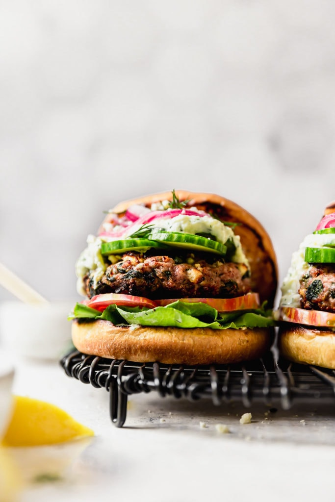 Feta Spinach Grilled Turkey Burgers on a wire serving tray. Burger is served in a bun with lettuce, tomato, cucumber slices, tzatziki sauce, red onion and dill.