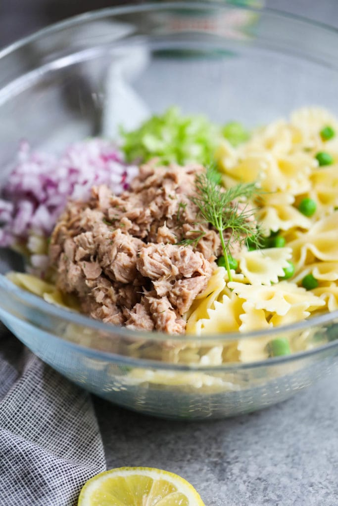 A clear glass bowl filled with pasta, veggies, tuna and fresh dill to make a tuna pasta salad.