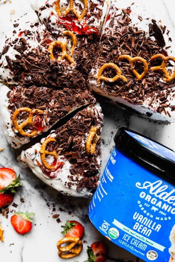 An ice cream pie with chocolate shavings, pretzels and berries on a white-grey slab of marble with a blue container of Alden's Organic Vanilla Bean Ice Cream next to it.
