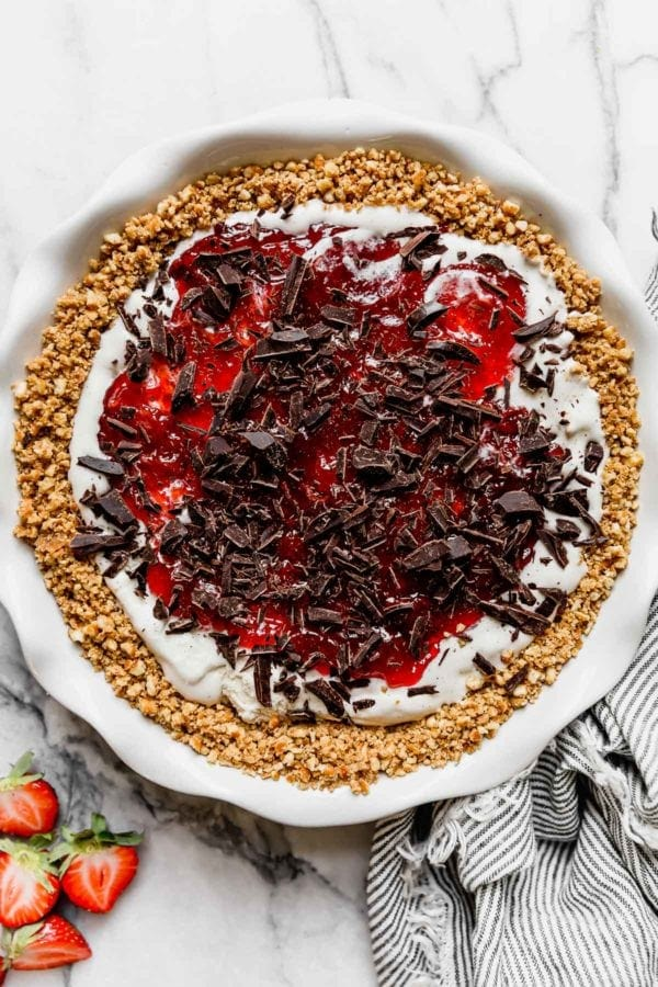 The first layer of vanilla ice cream, strawberry jam, and dark chocolate shavings in a pretzel crust.