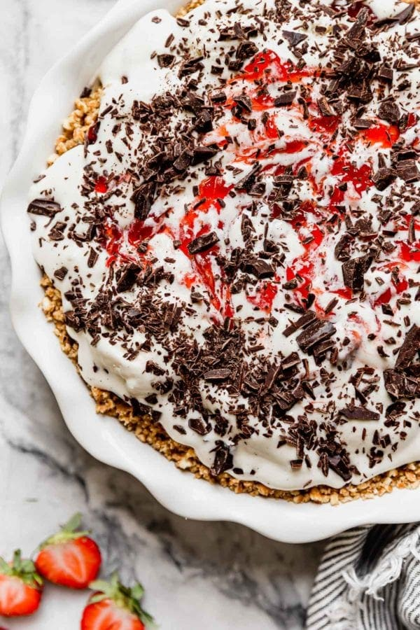 The second layer of the ice cream pie is added with a strawberry jam swirl and liberal dusting of chocolate shavings.