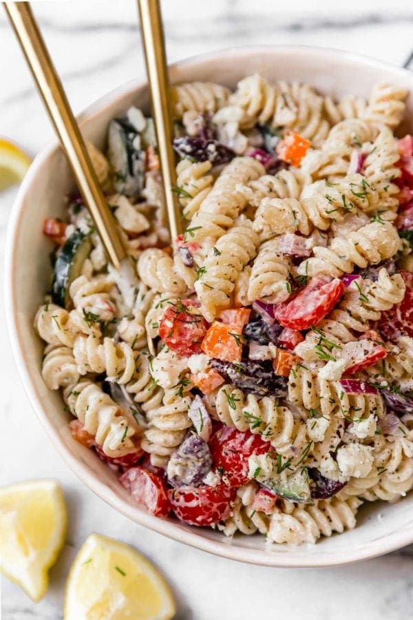 Easy Greek Veggie Pasta Salad in a white bowl and topped with fresh dill.