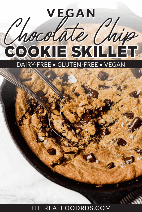 Warm and soft healthy chocolate chip cookie skillet still in the cast iron pan with two spoons for sharing.