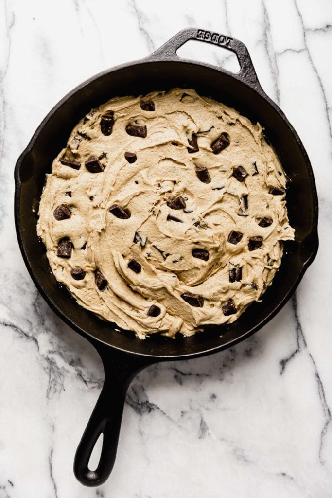 Vegan Chocolate Chunk Cookie dough is spread into a cast iron skillet and ready to bake.