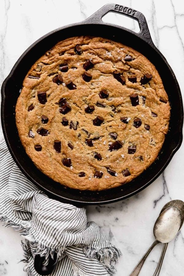 Baked Chocolate Chip Cookie Skillet in a cast iron pan sprinkled with sea salt fresh from the oven.