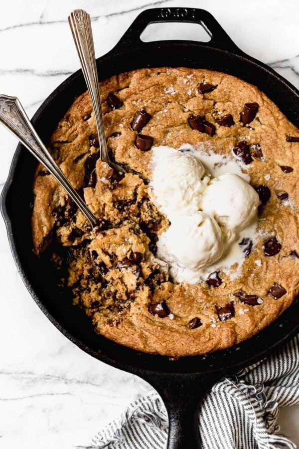 Soft and chewy chocolate chip cookie baked in a cast iron skillet with half melted ice cream on top.