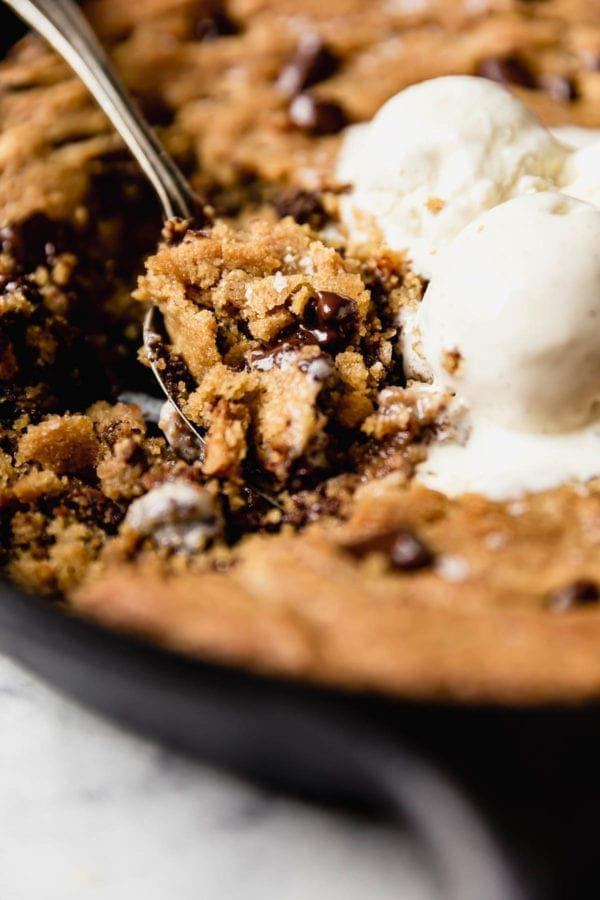 The perfect bite... a big spoonful of soft chocolate chip cookie skillet warm from the oven and topped with slightly melted vanilla ice cream