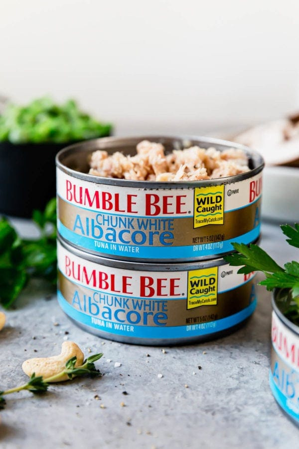 Two cans of Bumble Bee Chunk White Albacore Tuna stacked on top of one another. The top can is open to show the tuna inside.