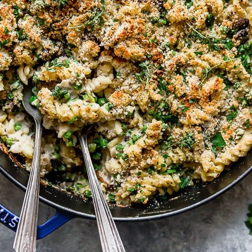 Creamy gluten free tuna noodle casserole in a blue cast iron skillet with two spoons in the casserole ready to serve