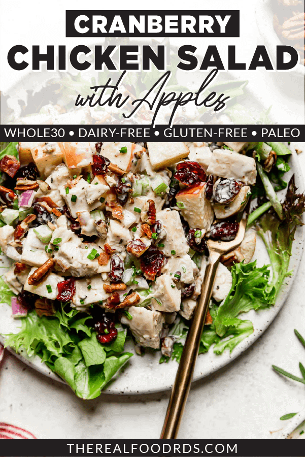 Creamy cranberry chicken salad topped with toasted pecans on a bed of mixed greens on a cream speckled plate.
