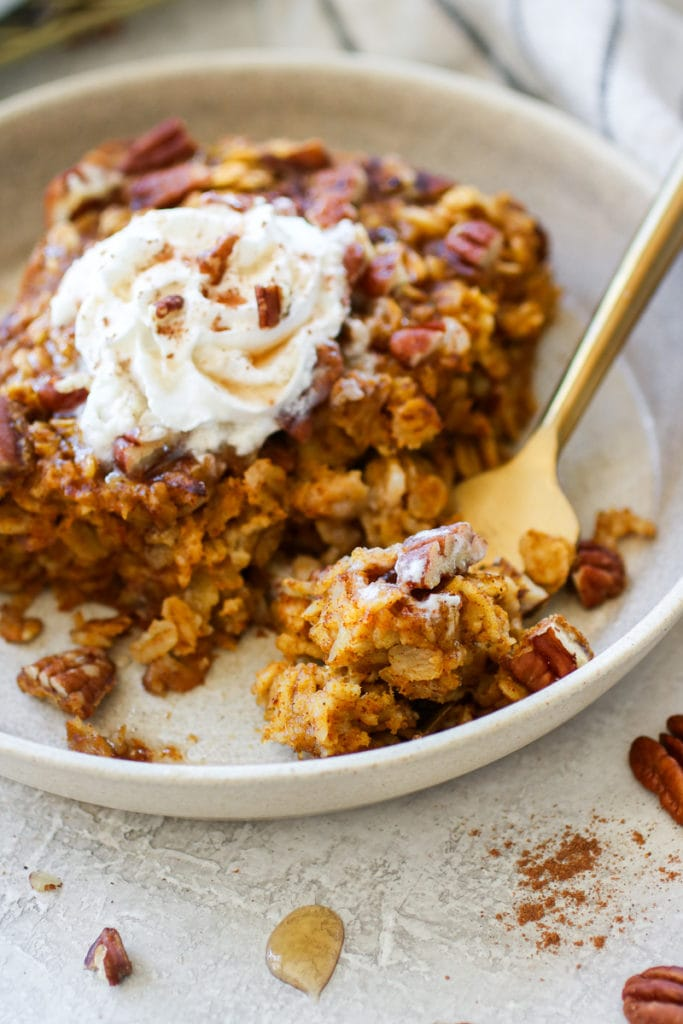 Serving of Pumpkin Baked Oatmeal on a light-colored plate topped with whipped topping, maple syrup and chopped pecans. Gold fork also on the plate holding a bite.