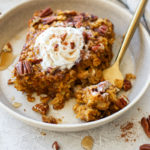 Gluten-free pumpkin baked oatmeal on a cream plate with a gold fork and topped with whipped cream and pecans.