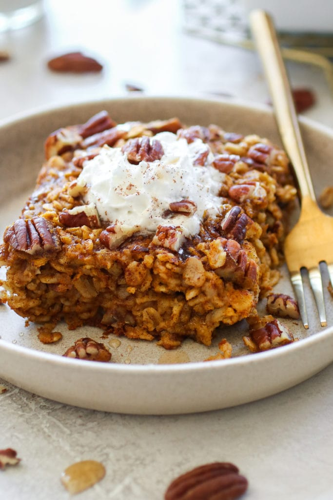 Serving of Pumpkin Baked Oatmeal on a light-colored plate topped with whipped topping, maple syrup and chopped pecans. Gold fork also on plate.