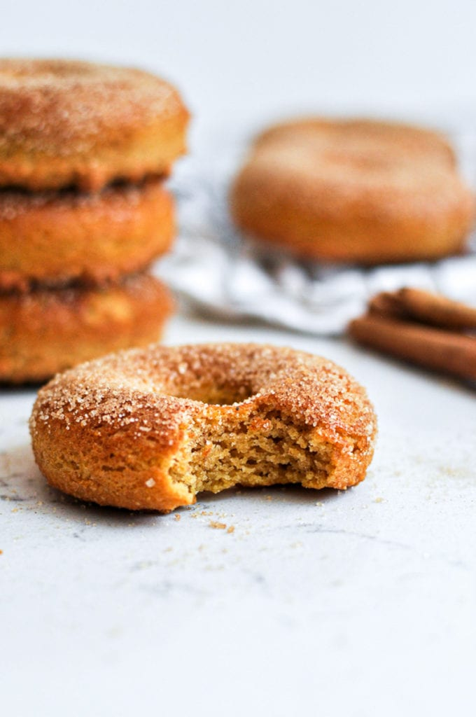 Healthy Baked Pumpkin Donuts with a bit taken out of it with a stack of three pumpkin donuts behind it.