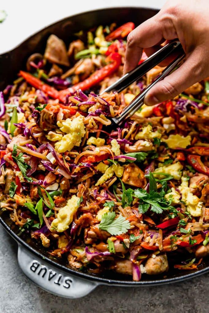 Healthy Chicken Pad Thai in a large cast iron skillet being served with a tongs.