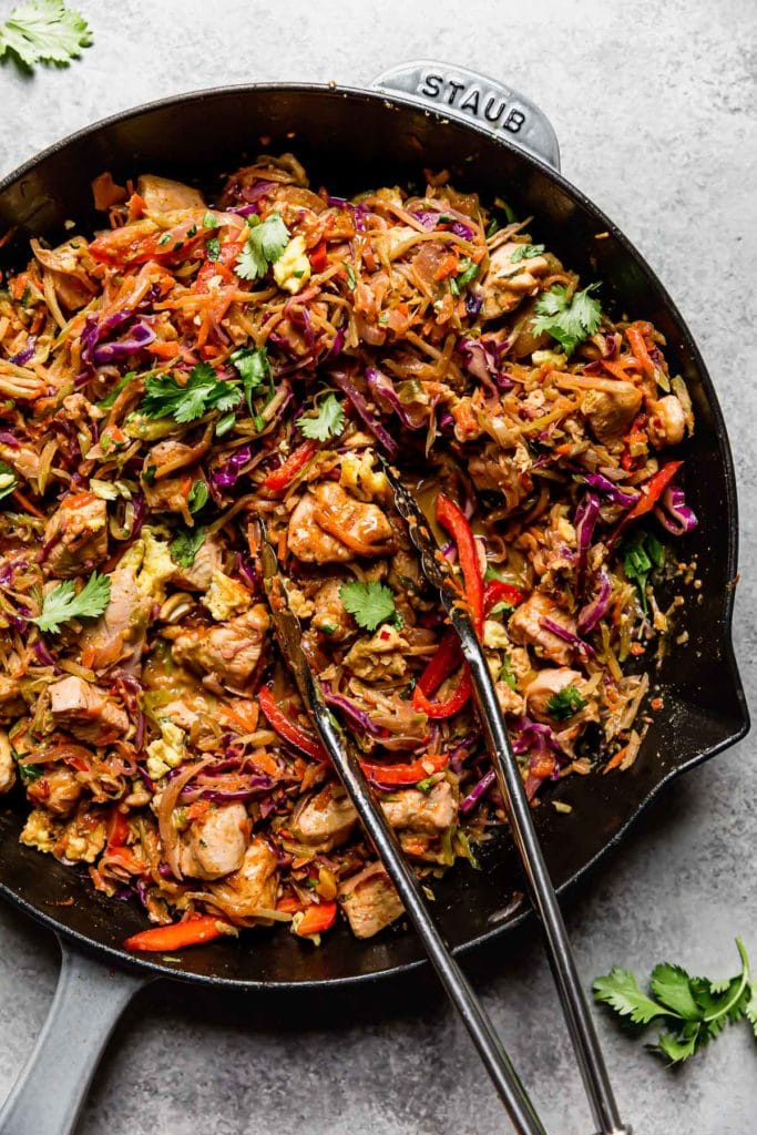Healthy Chicken Pad Thai in a large cast iron skillet with a serving tongs.