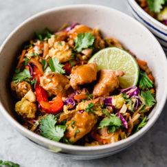 Veggie Chicken Pad Thai in a creamy bowl and topped with cashews and lime wedges.