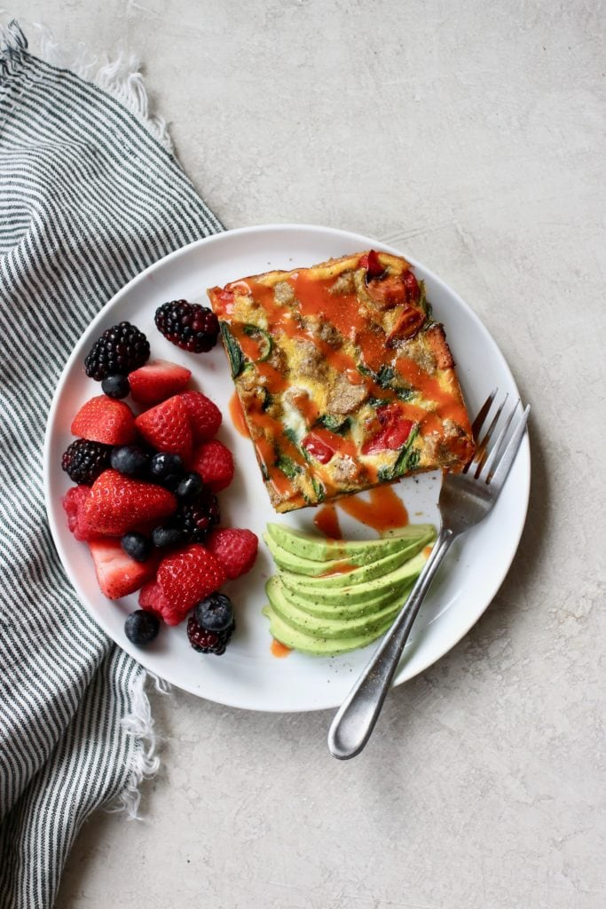 Egg bake with hot sauce drizzled on top, fresh berries, and slices of avocado on a white plate