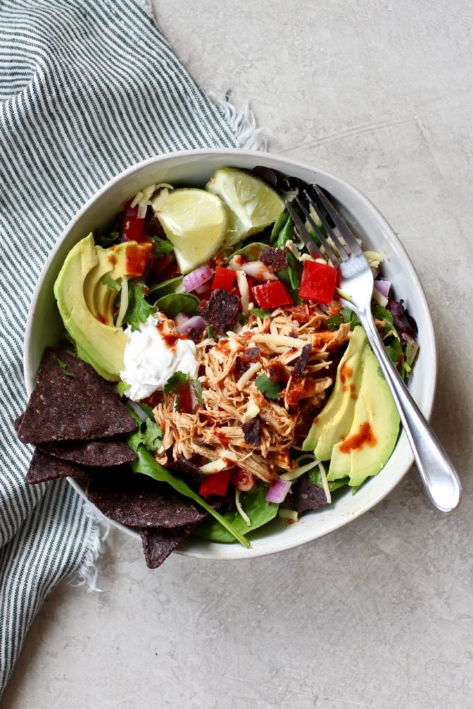 Shredded chicken over a mixed green salad and topped with avocado, lime, and blue chips in a white bowl