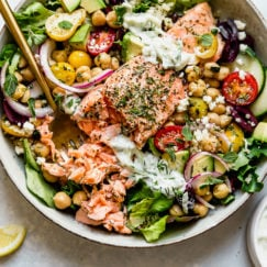 Mediterranean bowl with salmon fillet in a speckled bowl topped with tzatziki sauce