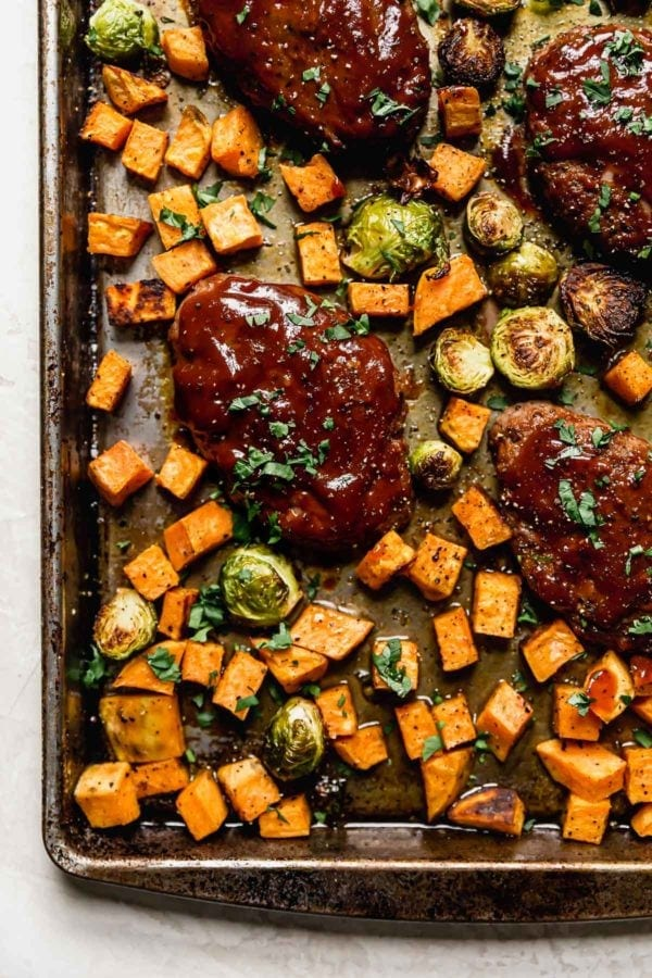 A close up of a mini meatloaf with roasted sweet potatoes and brussels sprouts on a baking sheet.
