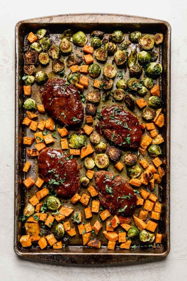 Mini bbq meatloaves and roasted sweet potatoes and brussels sprouts on a baking sheet