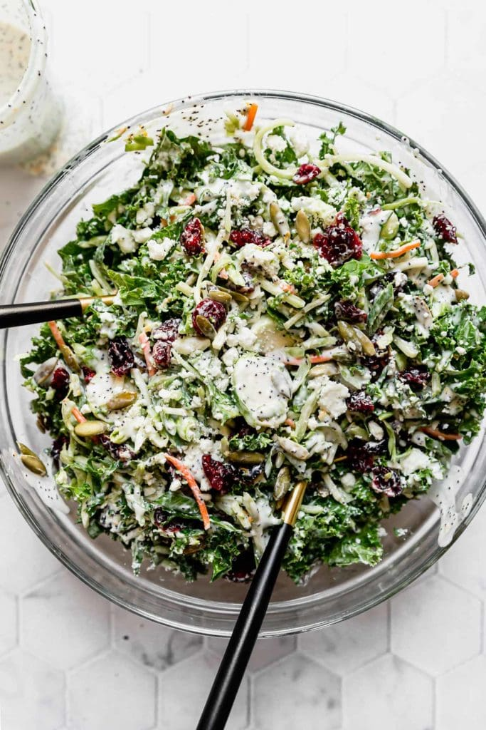 Sweet Kale Salad in a large clear bowl along with salad tossing utensils.