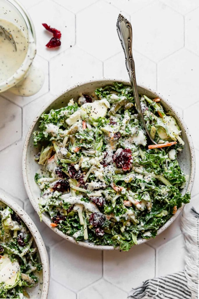 Sweet Kale Salad in a white speckled bowl with a silver fork in the salad.
