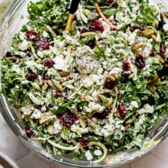 Sweet kale salad tossed in dressing in a clear glass bowl
