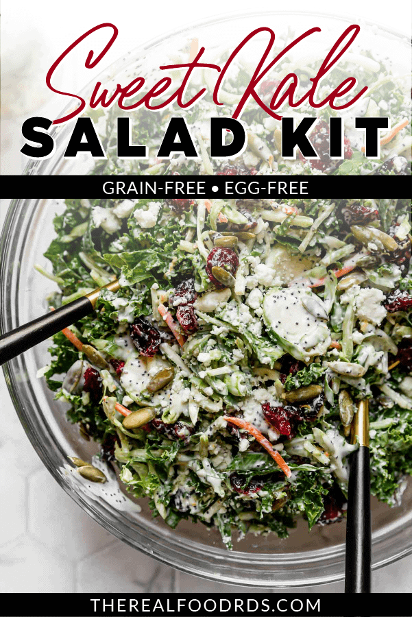 Sweet kale salad tossed in a yogurt poppyseed dressing in a clear glass bowl with two black serving spoons in the salad.