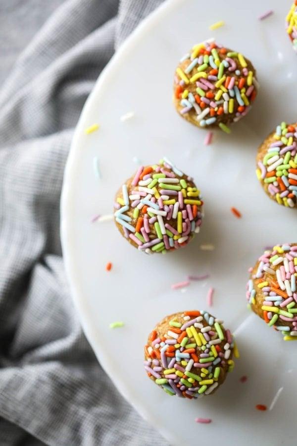Overhead shot of no bake energy bites with sprinkles on a white cake platter