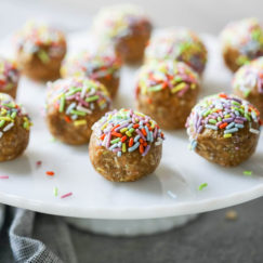 A white cake platter filled with vanilla birthday cake energy bites topped with colored sprinkles