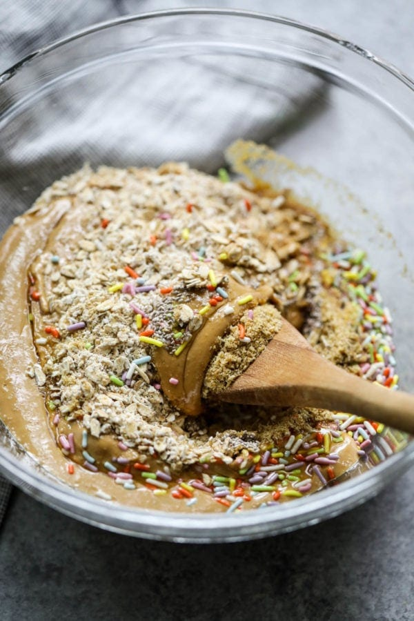 using a wooden spoon to mix together ingredients for birthday cake cookie dough bites