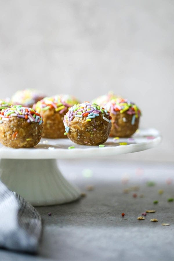 close up of vanilla cake energy bites with sprinkles on a white cake platter