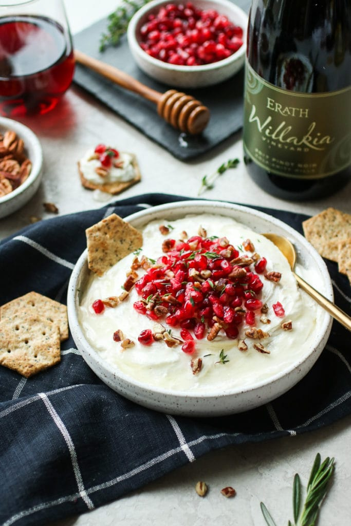 Whipped Goat Cheese in a white serving bowl, topped with pomegranate, fresh thyme and served with crackers.