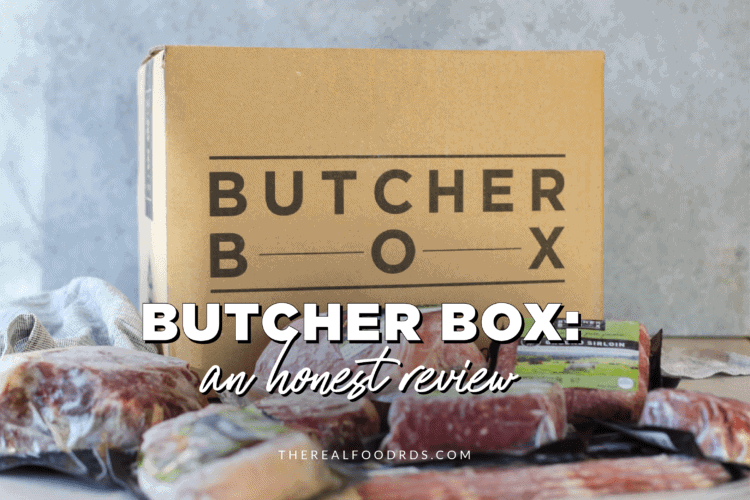 A large cardboard box with 'Butcher Box' written on the side with a variety of packaged meat in front.